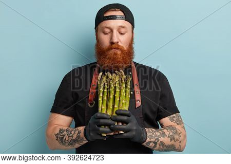Half Length Shot Of Bearded Red Haired Man Holds Fresh Green Delicious Asparagus In Hands, Prepares