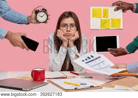 Sad Female Workaholic Keeps Hands Under Chin, Busy Making Project Work, Studies Papers, Wears Elegan