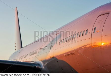 Close-up Of The Fuselage Of A White Passenger Airplane In The Evening Sun