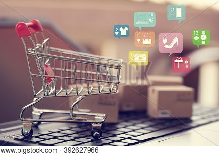 Shopping Online, E-commerce Concept:  Paper Shopping Bags On Notebook Keyboard. Depicts Purchase Of