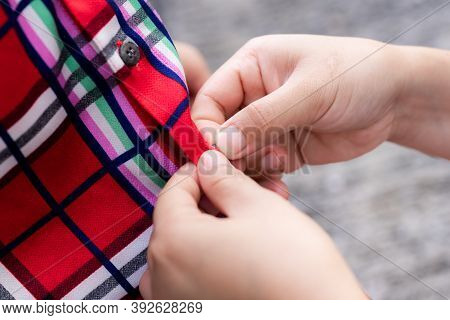 A Child Gets Dressed Up With The Help Of His Parents, Can Be Buttoned On The Shirt. Mother Helps Her