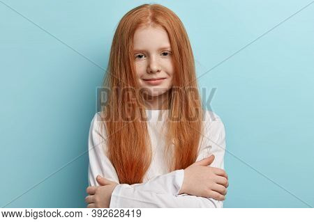 Tender Freckled Redhead Girl With Long Straight Hair, Hugs Herself, Wears White Jumper, Looks With G