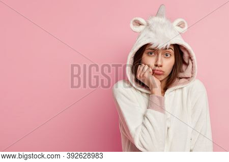 Headshot Of Dissatisfied Lovely Woman Purses Lips, Holds Hand Under Chin, Wears Uncorn Costume, Feel