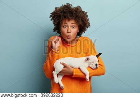 Emotive Funny Young Lady With Dark Skin, Keeps Lips Folded, Raised Clenched Fist, Carries Little Whi