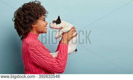 Photo Of Cheerful Loving Female Stands Sideways, Holds Little White Puppy Near Face, Teases And Want