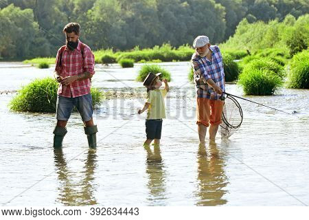 Happy Grandfather, Father And Grandson With Fishing Rods On River Berth. Fishing In River. Family Bo