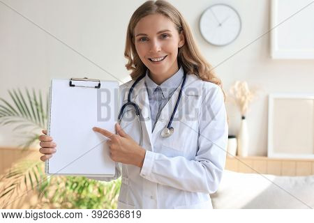 Young Beautiful Female Doctor In White Coat With Phonendoscope. Doctor Make Video Call Interact Thro