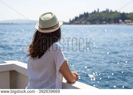 Traveler Girl In White Dress On Boat In Vacation. Young Girl Traveler On Boat On Sea. Traveler Girl