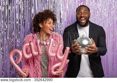 Horizontal Shot Of Happy Female And Male Clubbers Have Party, Fun In Nightclub, Hold Balloons And Di