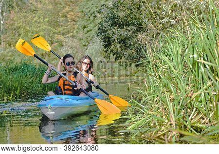 Family Kayaking, Mother And Daughter Paddling In Kayak On River Canoe Tour Having Fun, Active Weeken