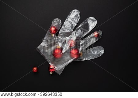Christmas lockdown concept. Christmas balls in a protective glove on a black background. Celebrating during the Covid-19 coronavirus pandemic
