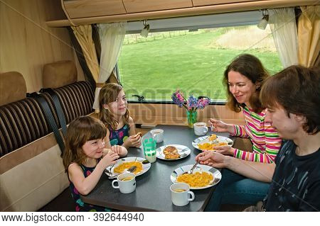 Family Eating Together In Rv Interior, Parents And Kids Travel In Motorhome (camper, Caravan) On Fam