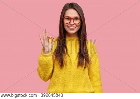 Everything Is Alright And Under Control. Happy Positive Woman Shows Okay Gesture, Demosntrates Appro