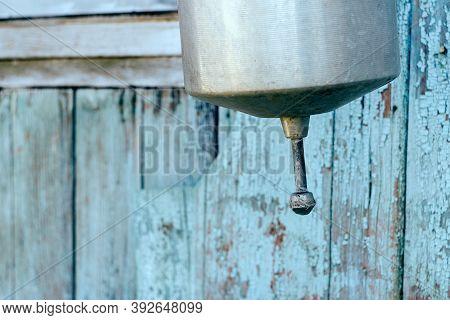 Aluminum Washbasin Hanging On Peeling Blue Wooden Wall