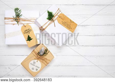 Christmas Gift Box With Greeting Tag - Christmas Present And Pine Leaves Decoration On White Wood Ta