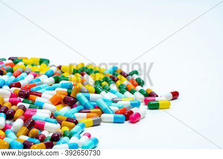 Selective Focus On Pile Of Multi-colored Antibiotic Capsule Pills. Antimicrobial Capsule Pills On Wh