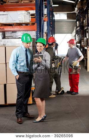 Female supervisor and male colleague using digital tablet with foremen communicating at warehouse
