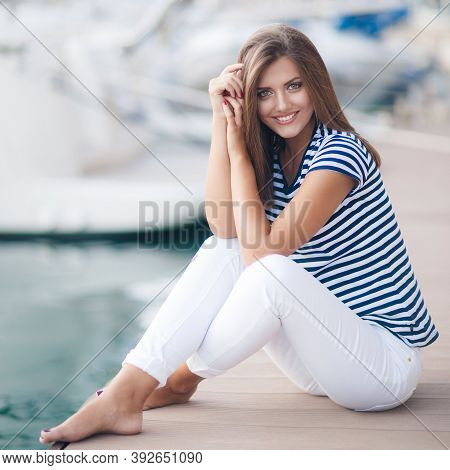 Pretty Girl With Long Beautiful Hair Happy Smile While Sitting Outdoor With Boats On Background. Por