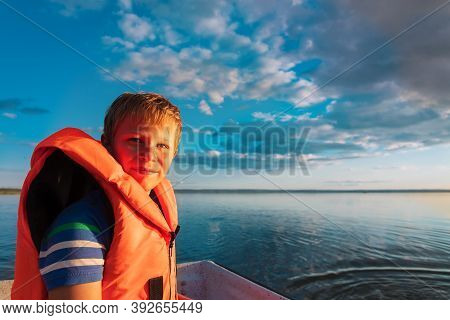 Happy Kid In Life Jacket On Boat Ride In Lake