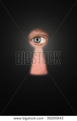 Creepy man peeking through a keyhole with focus on his eyeball.