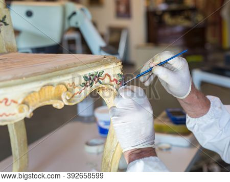 Hands Of A Restorer With Gloves And Brush: Working On The Restoration Of A Chair.