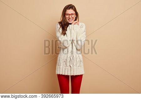Studio Shot Of Pleased European Woman Feels Pleasure, Enjoys Compliment, Smiles Broadly, Shows White