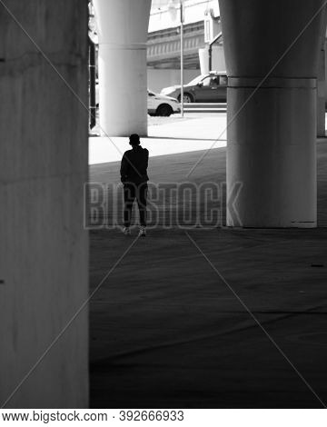 A Human Silhouette Among Giant Concrete Pillars Under A Road Bridge. The Concept Of Insignificance O