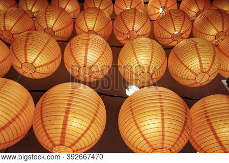 A Round Of Beautiful Chinese Lanterns Hanging On A Wire And Glowing In The Dark Night For A New Year