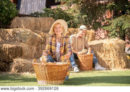 Female Standing On Knees Near Basket With Cobs, Male Farmer Shucking Cobs Behind Her