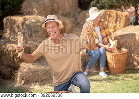 Happy Male Farmer Showing Cobs Into The Camera, Female Farmer Shucking Cobs Behind Him