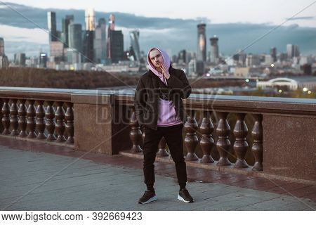 Handsome Casual Man In Black Jacket And Pink Hoody Standing On A Skyscraper View. Dusk Time
