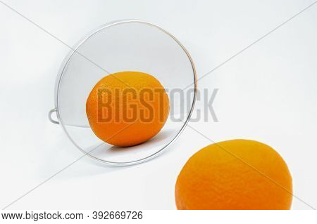 Reflection Of Orange With Thick Peel In Cosmetic Mirror On White Background. Metaphor Of Cellulite T