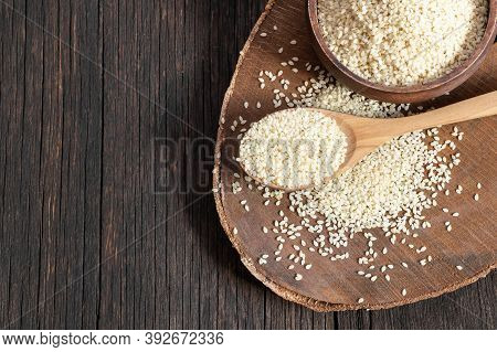 Raw Sesame Seeds In Wooden Shovel On Wooden Rustic Table. Uncooked Sesame Background Concept With Co