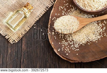 Glass Bottle Of Sesame Oil And Raw Sesame Seeds In Wooden Shovel On Wooden Table. Uncooked Sesame Ba