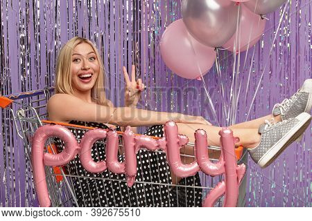 Horizontal Shot Of Happy Blonde Female In Shopping Cart, Makes Peace Gesture, Wears Dress And Sports