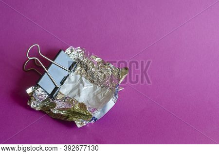 Smashed Candy Wrappers And Metal Black Binder Clip On  Purple Background. Binder Clip Clamps Random
