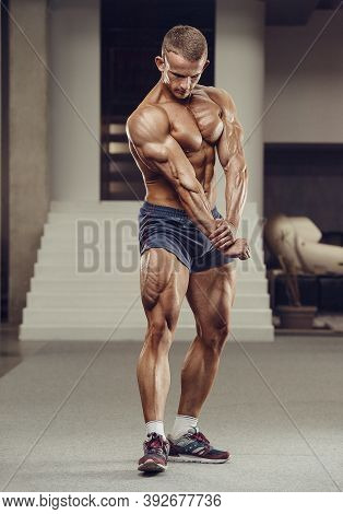 Caucasian Power Athletic Man Training Pumping Up Leg Quadriceps Muscles. Strong Bodybuilder With Six