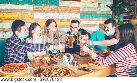 Happy Young Friends With Protective Face Masks Eating And Drinking Beer Together At Restaurant - New