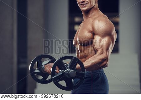 Caucasian Power Athletic Man Training Pumping Up Biceps Muscles. Strong Bodybuilder With Six Pack, P