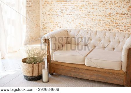 Rustic Livingroom Interior With White Sofa And Wicker Basket With Dried Flowers. Cozy Autumn Interio