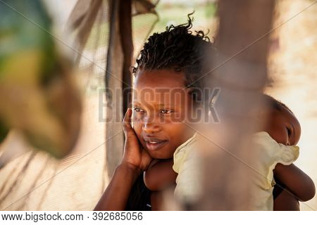 african street vendor, mother holding her child between the bags of peppers in the shed