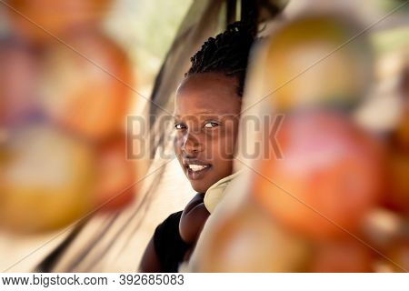 african street vendor, mother holding her child between the bags of tomatoes