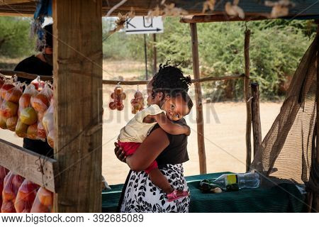 african street vendor serving a client , mother holding her child bags of tomatoes hanging in the shed