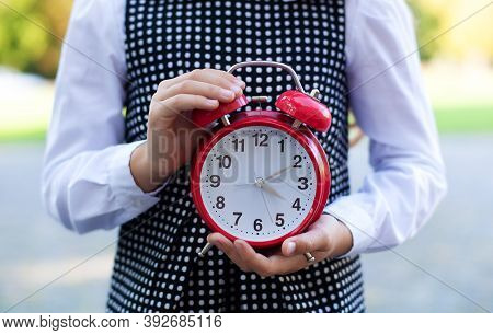 Child Holding Big Red Alarm Clock In Two Hand. Photo Of Female Hands Holding Alarmclock. Copy Space.