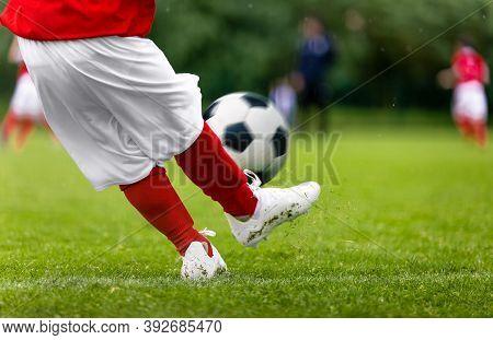 Football Kick. Young Player Kicking Soccer Ball On Green Grass Turf Field. Closeup Of Footballers Fe