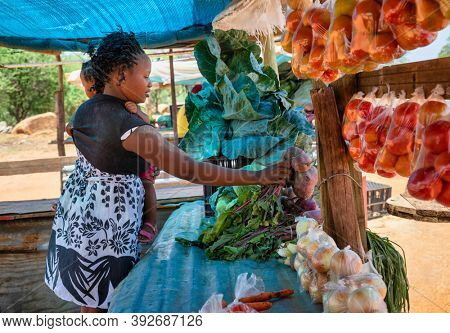 african street vendor, mother holding her child between the bags of cabbage and tomatoes in the shed