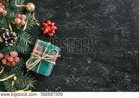 Christmas And New Year Holiday Background With A Gift Box, Fir Tree Branches And Seasonal Decoration