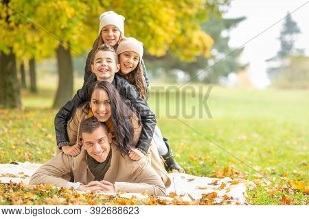 Family With Children Lying Down On A Blanket Making A Human Pyramid In The Nature On A Fall Day.
