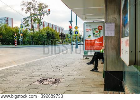 Moscow. Russia. September 4, 2020 Legs Of A Man Sitting On A Bench At A Public Transport Stop. Waiti
