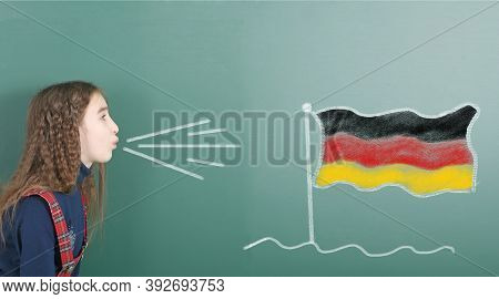 Pre-adolescent Girl Blowing On The School Board Drawn On The Blackboard Germany Flag. High Resolutio